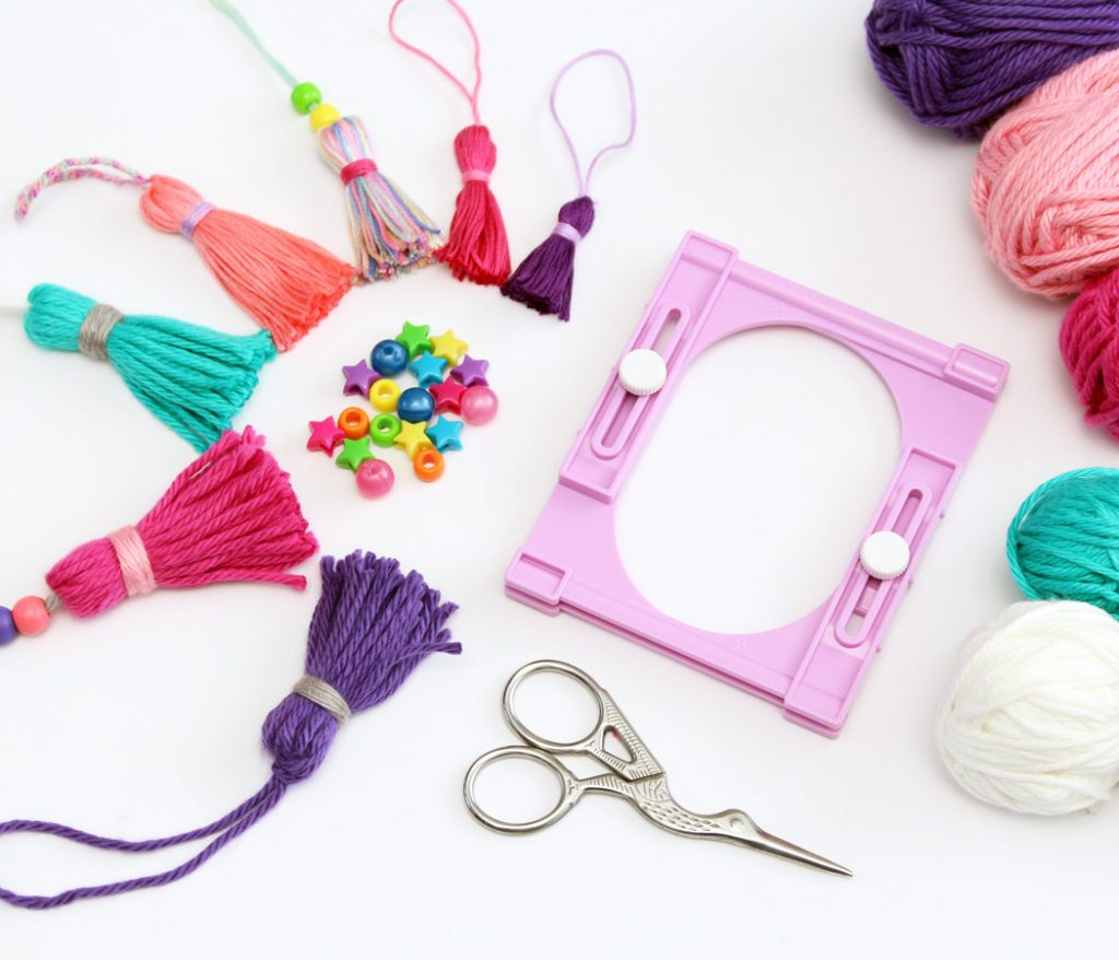 Clover Tassel Maker with tassels, beads, and yarn